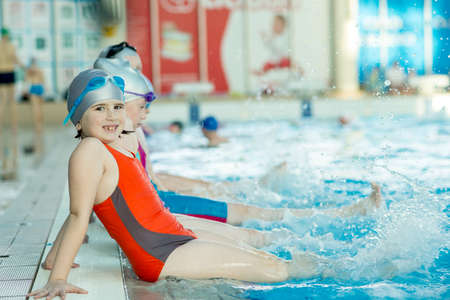 happy children kids group at swimming pool class learning to swim Stock Photo