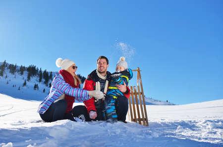 gelukkige jonge familie spelen in verse sneeuw op mooie zonnige winterdag buiten in de natuur Stockfoto