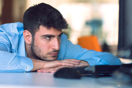 overworking: Portrait of a depressed office worker laying on his desk and thinking