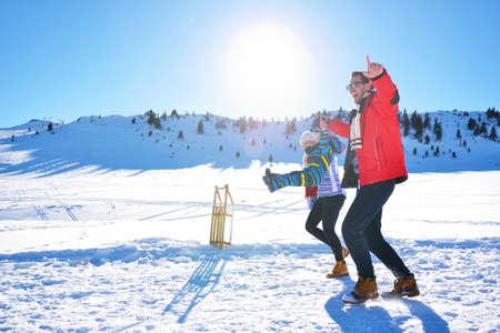 palle di neve: Giovane famiglia felice che gioca in neve fresca in bella giornata di sole invernale all'aperto in natura