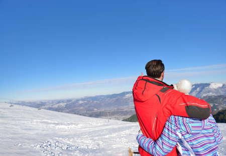 range hood: Rear view of a loving couple in fur hood jackets looking at snowed mountain range. Stock Photo