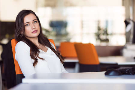 Happy pensive businesswoman planning and looking sideways at office Stock Photo