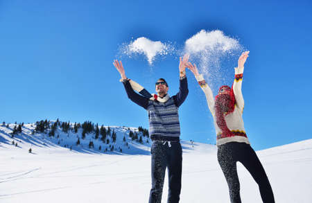 Carefree happy young couple having fun together in snow.