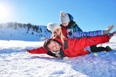 play the old park: happy young family playing in fresh snow at beautiful sunny winter day outdoor in nature