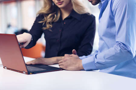 openspace: Young couple working together on a laptop in the office. Teamwork concepts.