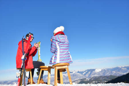 A couple is resting on lounges in picnic zone on european ski resort Stock Photo