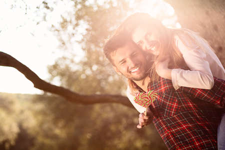 Portrait of smiling handsome man giving piggy back to his girlfriend in the nature Stock Photo