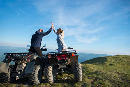 Beautiful couple is watching the sunset from the mountain sitting on quadbike Stock Photo