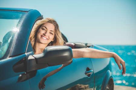 Gelukkige en zorgeloze vrouw in de auto op het strand