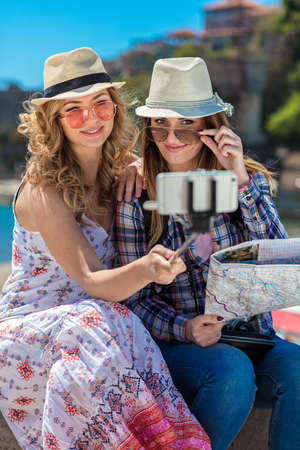 Two smiling young women sitting on a city bench making faces while taking self portraits together Stock Photo