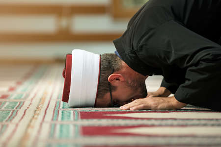 Young Imam praying inside of beautiful mosque