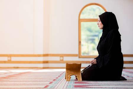 Young muslim woman praying in mosque Standard-Bild