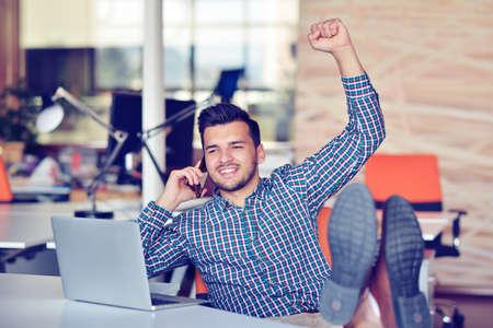 puños cerrados: Alegre joven en ropa casual manteniendo los brazos en alto y mirando feliz mientras está sentado en el escritorio en la oficina Foto de archivo