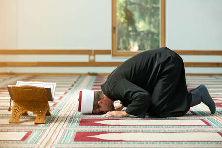 Young Imam praying inside of beautiful mosque
