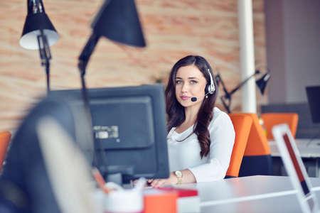 Jonge vrouw die in call centre werkt, dat door collega's wordt omringd Stockfoto