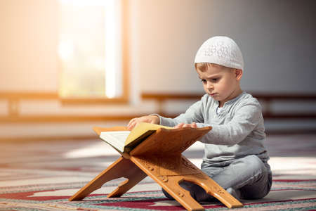 The Muslim child prays in the mosque, the little boy prays to God, Peace and love in the holy month of Ramadan.