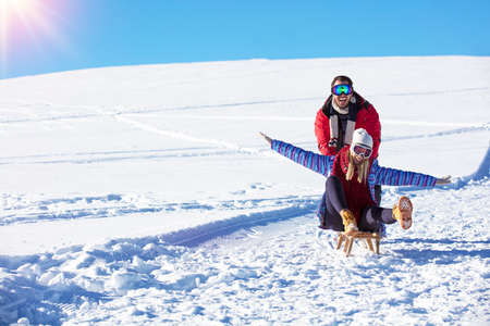 Young playful couple having fun sledging down snow covered hill Stock Photo