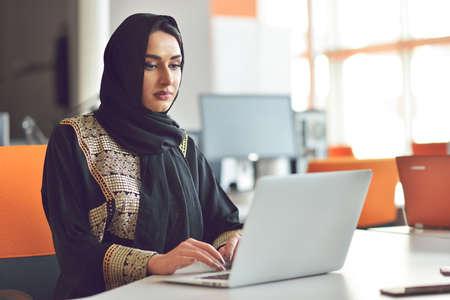 muslimische asiatische Frau arbeitet im Büro mit Laptop