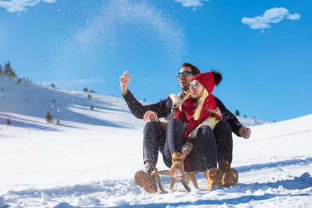 Young Couple Sledding And Enjoying On Sunny Winter Day