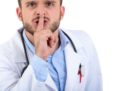 Young handsome doctor gesturing silence with his finger over his mouth isolated on white background
