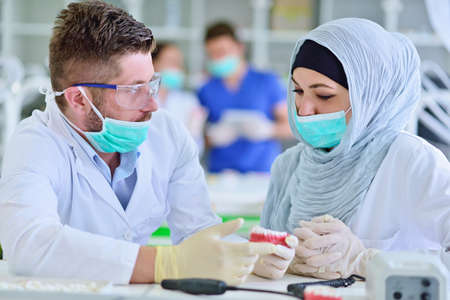 Arab students with hijab while working on the denture, false teeth.