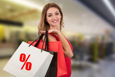 Shopping woman holding bags with discount symbol in shopping mall.