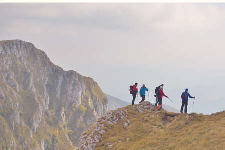 Group of People of different age and ethnicity walking up on Mountain Trail during Hike