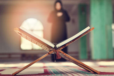 An open Holy quran with wood stand with praying people in background Stock Photo