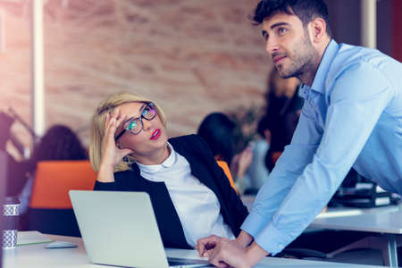 Skilled professional blonde female CEO explaining to young male employee requires and strategy Stock Photo