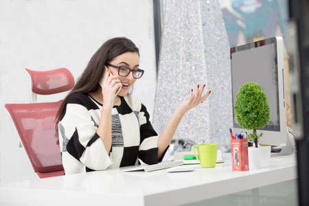 Single happy female business owner with smile and eyeglasses on phone and working on desktop computer 版權商用圖片