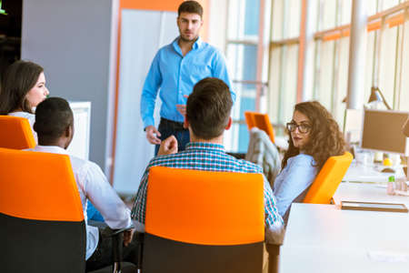 Groep terloops gekleed zakenlui die ideeën in het bureau bespreken.