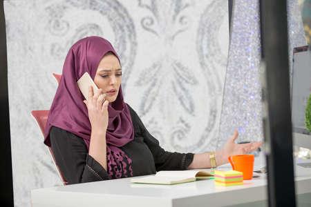 modern smart female Islamic office worker talking on phone