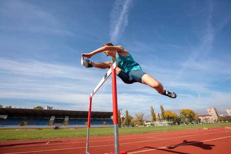 Niedrige Winkelsicht des entschlossenen männlichen Athleten, der über Hürden springt
