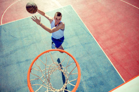 High angle view of basketball player dunking basketball in hoop Stock Photo