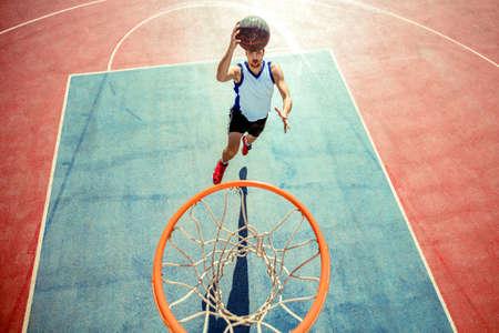 Vista dell'angolo alto di pallacanestro dunking del giocatore di pallacanestro in cerchio Archivio Fotografico