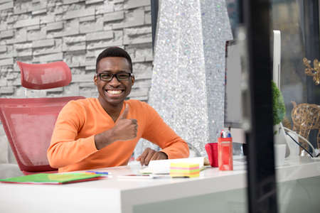 Happy excited businessman celebrate his success. Winner, black man in office reading on laptop, copy space Stock Photo