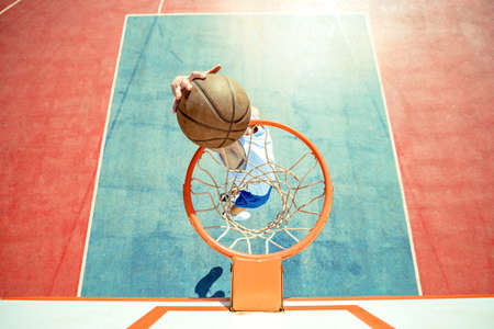Young man jumping and making a fantastic slam dunk playing streetball, basketball. Urban authentic.