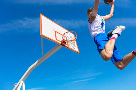 Young Basketball street player making slam dunk Stock Photo