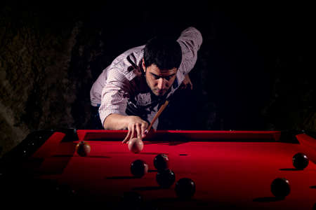 A man with a beard plays a big billiard. Фото со стока