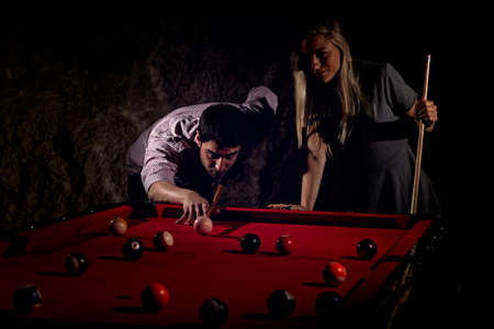 Young romantic couple playing billiard game