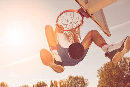 Street basketball player performing power slum dunk