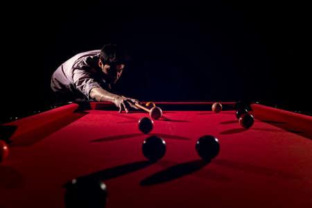 A man with a beard plays a big billiard. Stockfoto