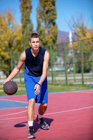 Handsome male playing basketball outdoor Stock Photo