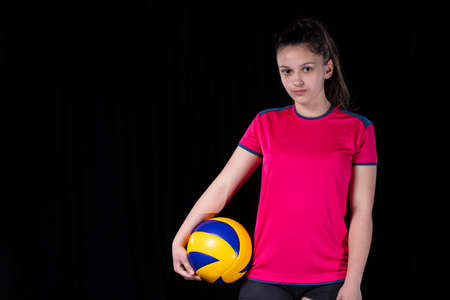 Indoor young volleyball woman player isolated on dark background