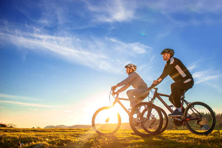 Happy mountainbike couple outdoors have fun together on a summer afternoon sunset Banque d'images