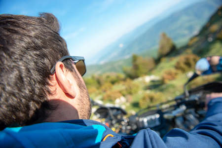 Young man on quad bike on a countryside trail. View from a quad bike. Stock Photo