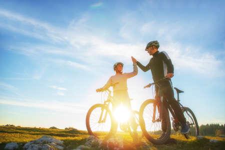 Het gelukkige paar gaat op een bergweg in het bos op fietsen met helmen die elkaar een high five geven