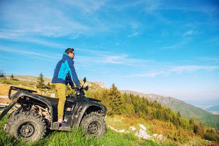 Man on the ATV Quad Bike on the mountains road.