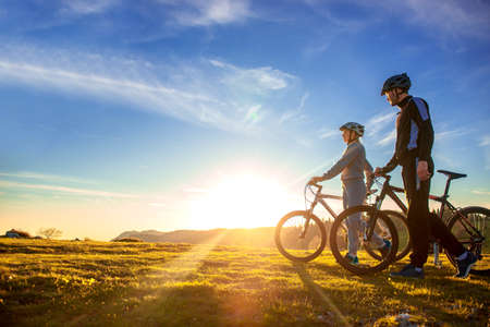 Happy mountainbike couple outdoors have fun together on a summer afternoon sunset Stock Photo