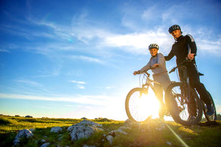 Cyclist couple with mountain bikes standing on the hill under the evening sky and enjoying bright sun at the sunset.